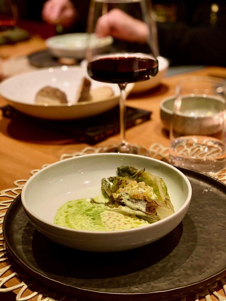 Veles Restaurant Nürnberg kurzgebratenes Salatherz mit einer Vinaigrette aus Saiblings-Rogen, Joghurt und Dill mit Rotwein im Hintergrund
