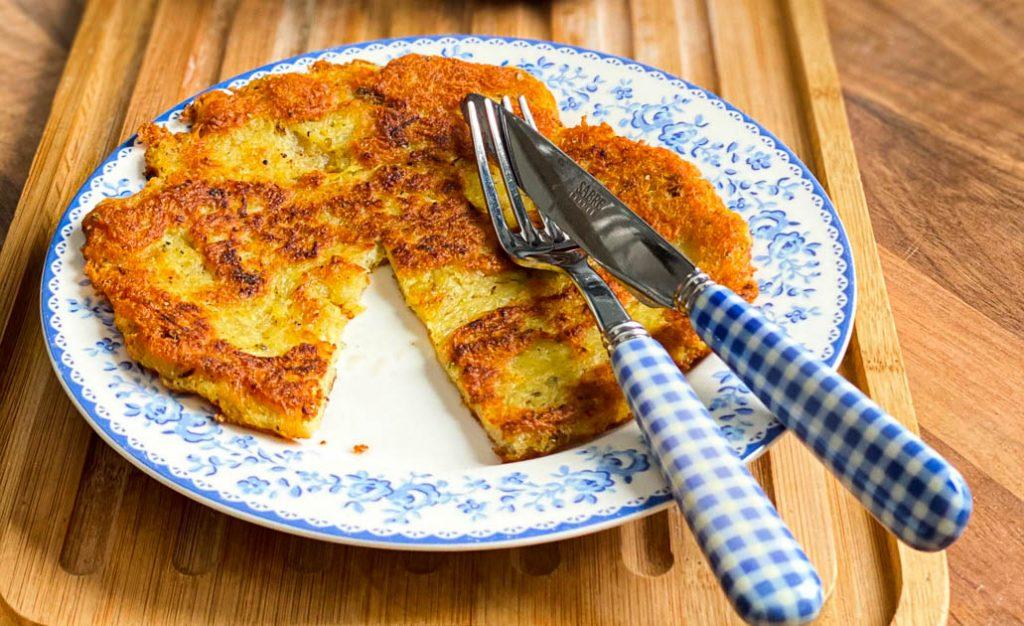 Knusprige Kartoffelrösti angeschnitten auf einem Teller.