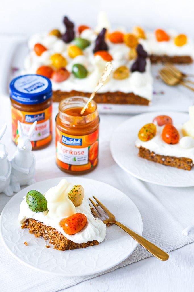 Low Carb Carrot Cake vom Blech, aufgeschnitten, daneben zwei Gläser Mintal Aprikose, eines offen