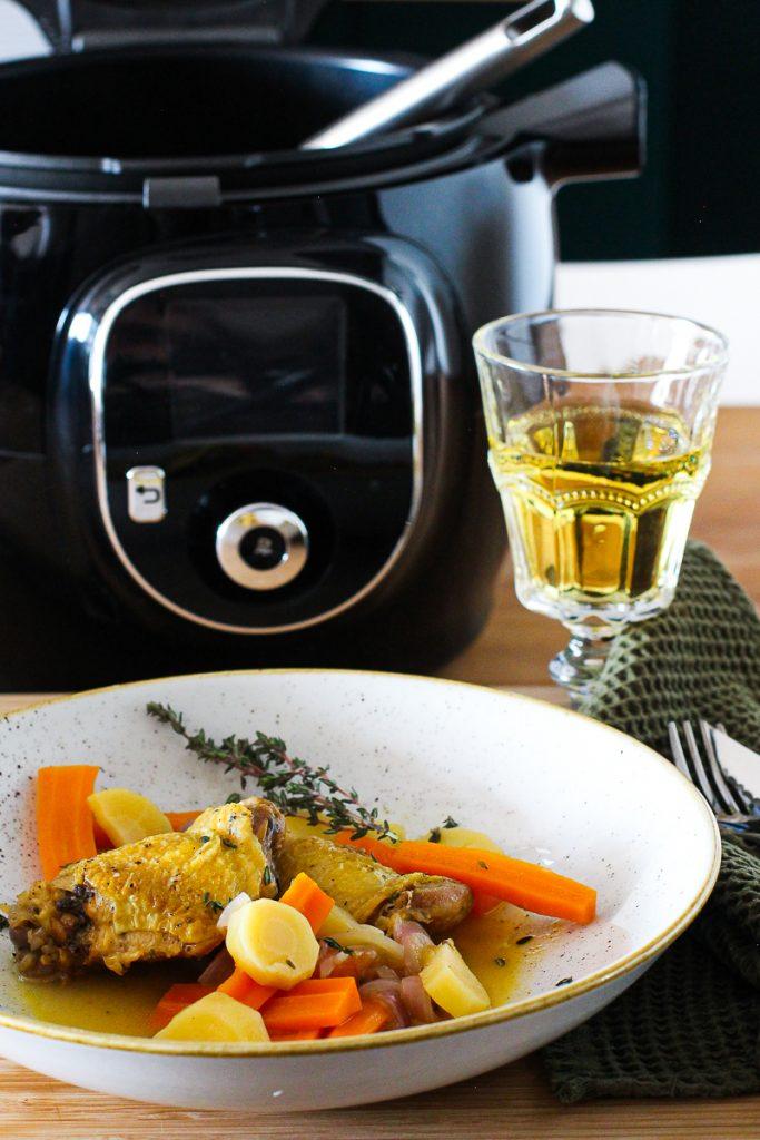Hähnchenkeulen in Cidre mit Thymian bestreut auf einem grauen Teller