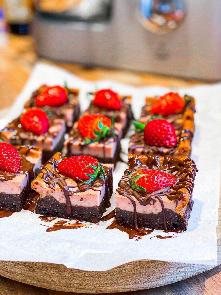Brownie-Cheesecake mit Erdbeeren ohne Mehl und Zucker auf einem Brett, aufgeschnitten