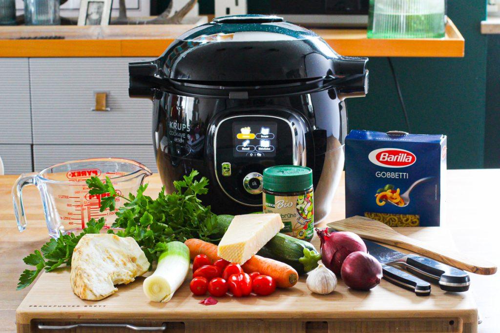 Zutaten für die schnelle Minestrone, das Gemüse ist auf einem Holzbrett vor der Cook4Me.