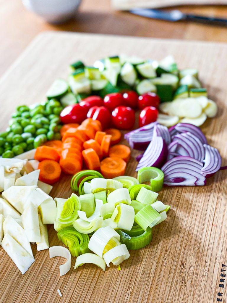 Geschnittene Karotten. Sellerie, Zucchini, Lauch, Zwiebeln, Knoblauch, Tomaten und Edamame auf einem Brett.
