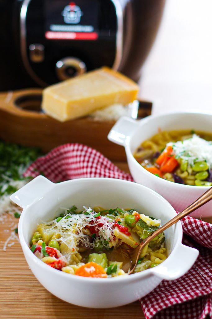 Schnelle Minestrone angerichtet in der Nahaufnahme mit Parmesan und Petersilie.