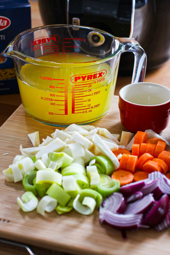 Zutaten für die Schnelle Minestrone - geschnittenes Gemüse und Brühe in einem großen Messbecher aus Glas.