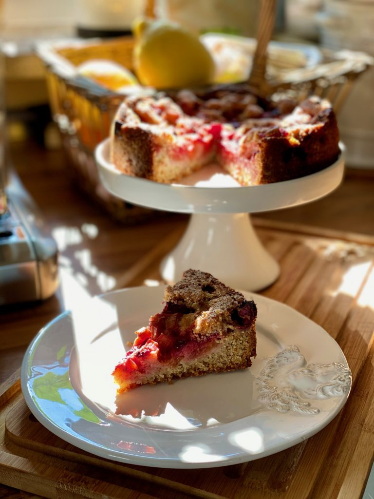 Einfacher Dinkel Vollkornkuchen mit Erdbeeren und Rhabarber, ein Stück abgeschnitten, im Hintergrund der ganze Kuchen