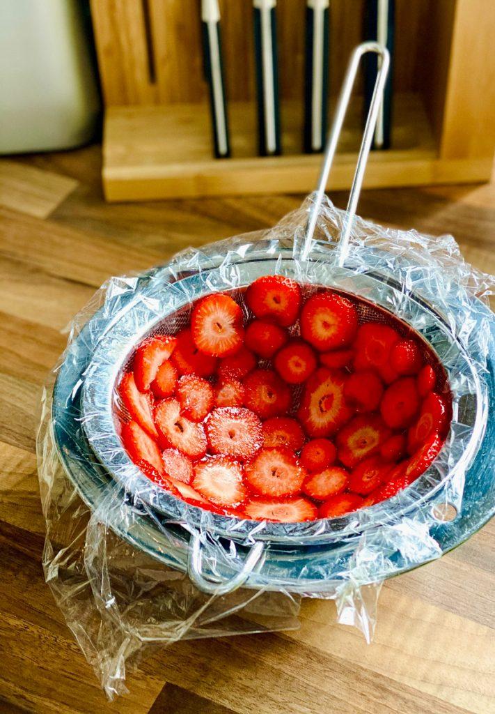 Erdbeerscheiben in einem mit Klarsichtfolie ausgelegtem Sieb