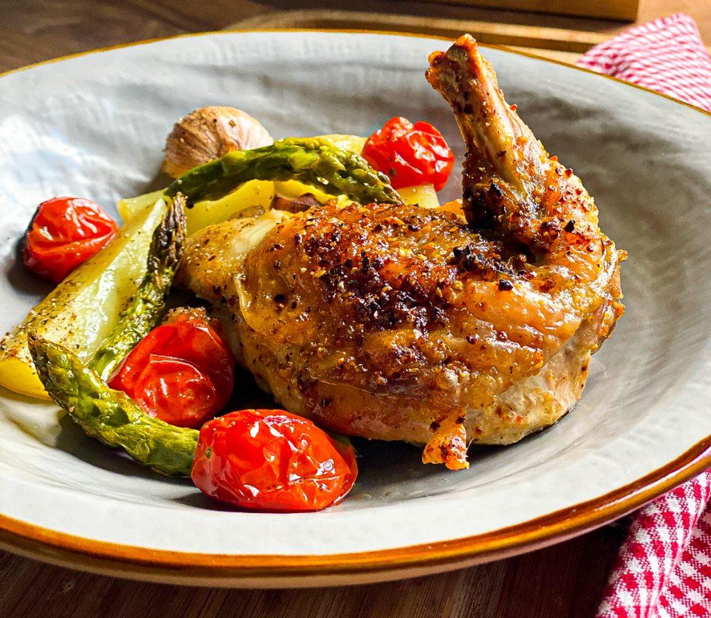 Huhn mit Spargel und Tomaten vom Blech, auf einem grauen Steingut Teller
