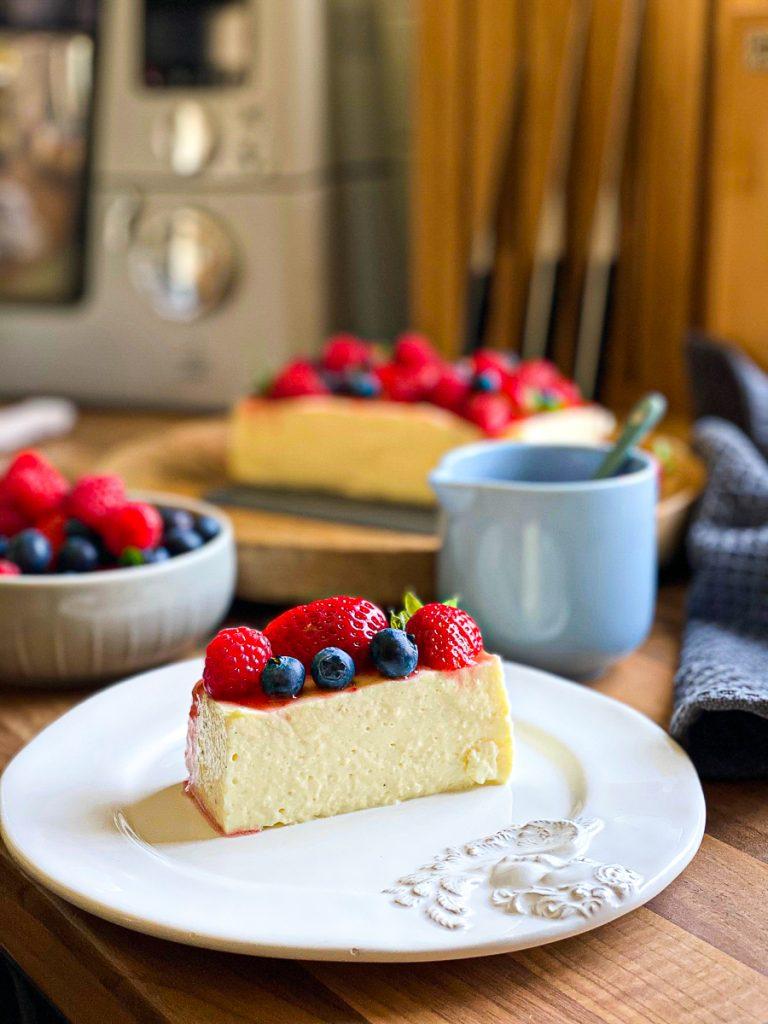 Pudding-Cheesecake mit Hüttenkäse zuckerfrei und fettarm, ein Stück auf einem weißen Teller mit Beeren