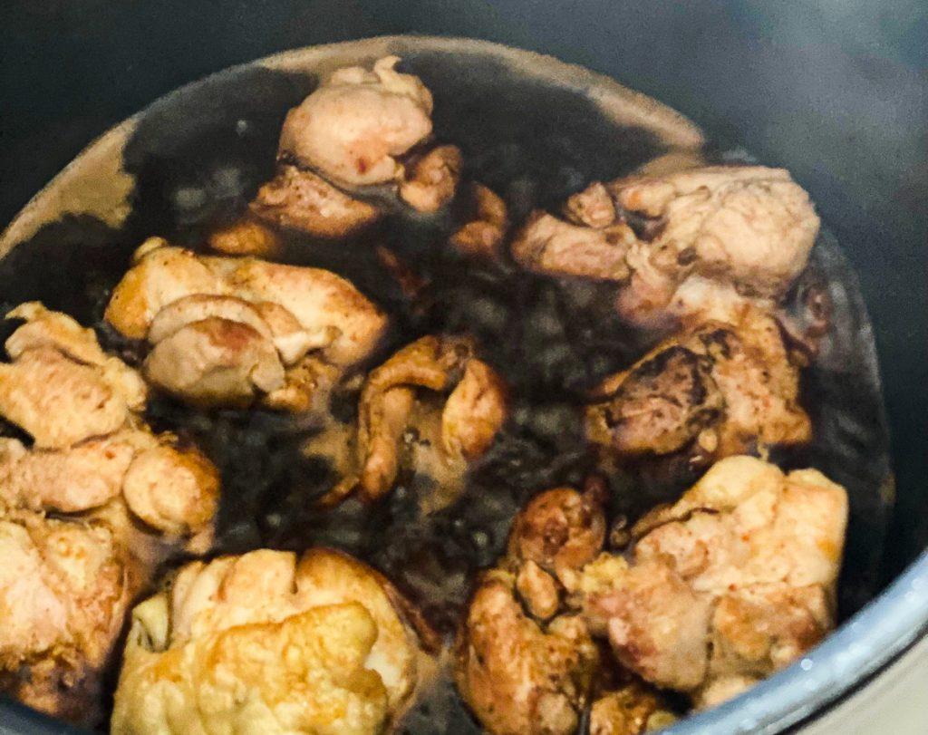 Das angebratene Hähnchenfleisch für das Pulled Chicken mit Fond aufgegossen