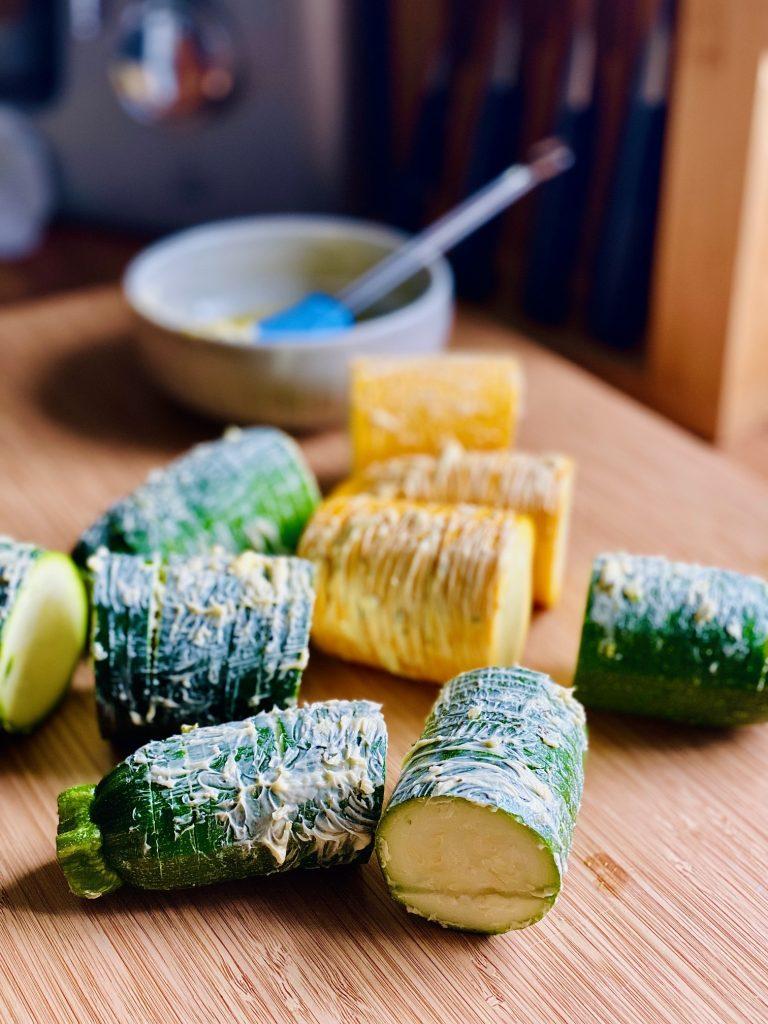 Hasselback Zucchini mit Kräuterbutter, vor dem Backen auf einem Brett