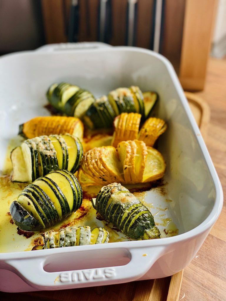 Hasselback Zucchini mit Kräuterbutter in einer weißen Auflaufform