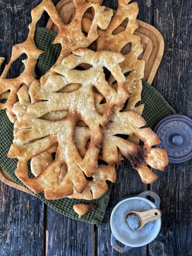 Französische Fougasse - die Provence in einem Brot - auf einem Holzbrett mit einem Salzbehälter
