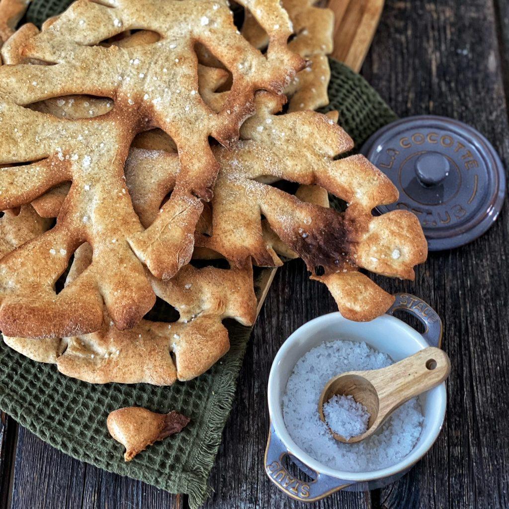 Französische Fougasse - die Provence in einem Brot - auf einem grünen groben Tuch mit Salzbehälter
