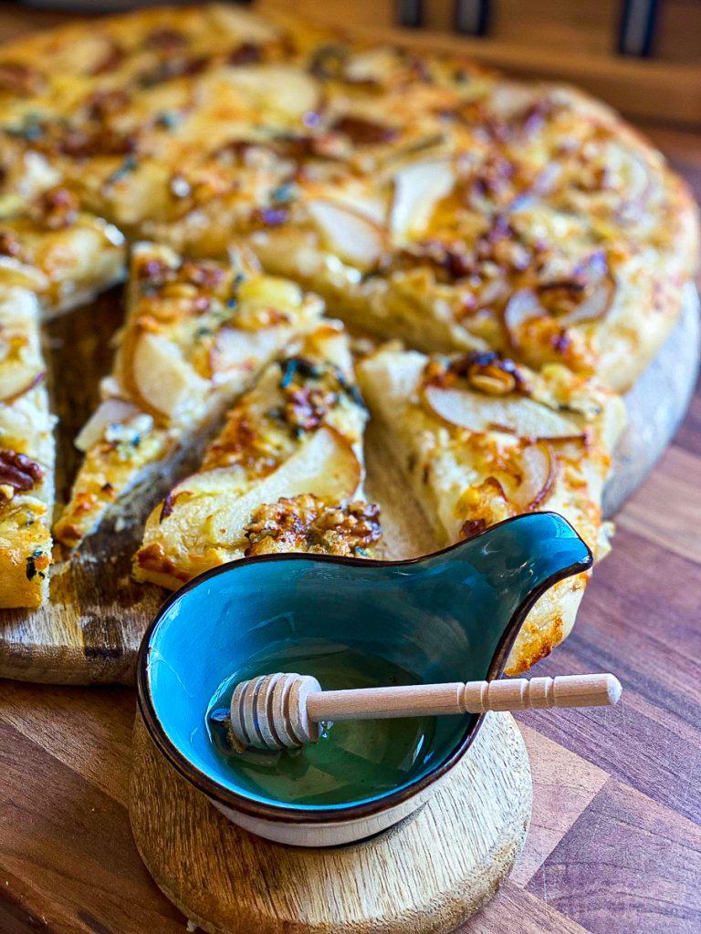 Knusprige Focaccia mit Birnen und Blauschimmelkäse, daneben ein Töpfchen mit Honig