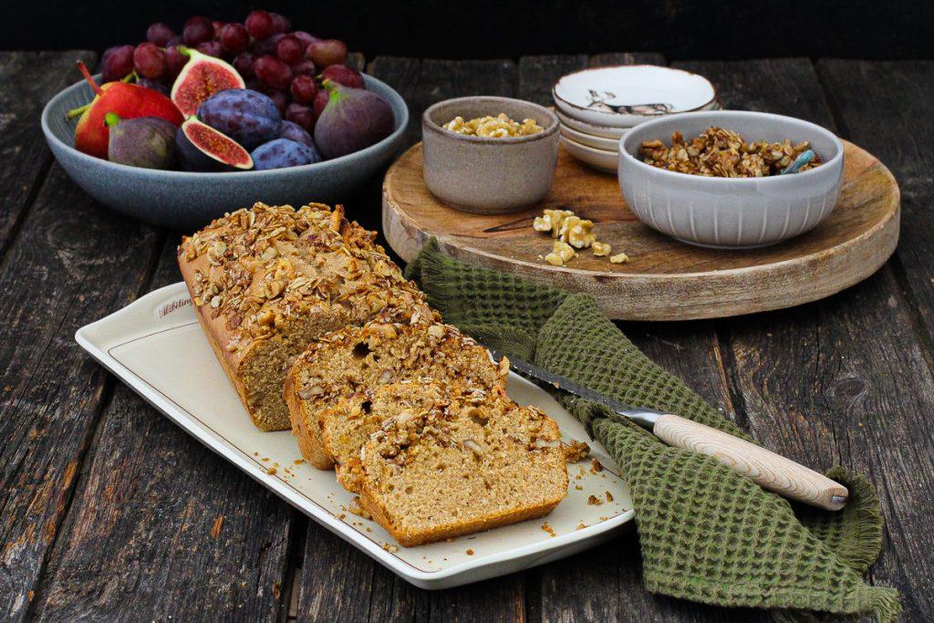 Walnuss-Granola-Kuchen auf geschnitten auf einem Tablett, dahinter Granola