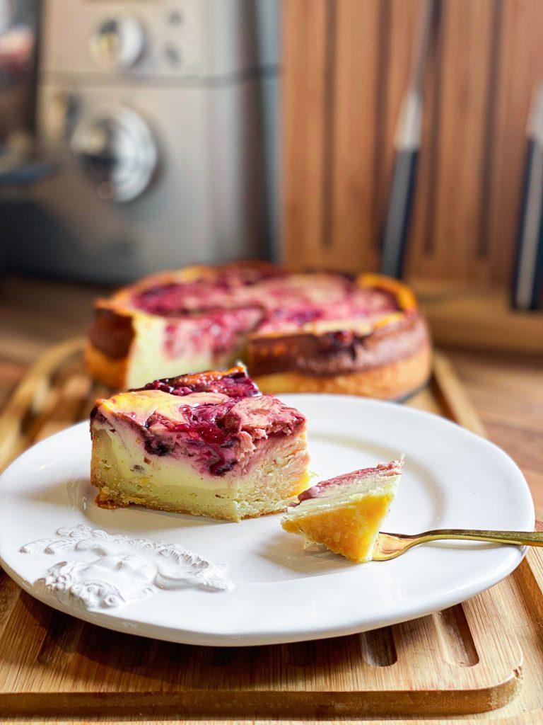Schlanker Zwetschgen Swirl Cheesecake. Ein Stück mit einer Gabel auf einem weißen Teller.